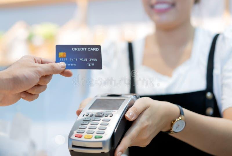 O cliente no café está pagando através do cartão de crédito ao assistente de loja imagem de stock royalty free