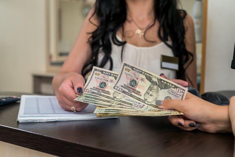 O cliente no salão de beleza dá dólares ao recepcionista imagem de stock