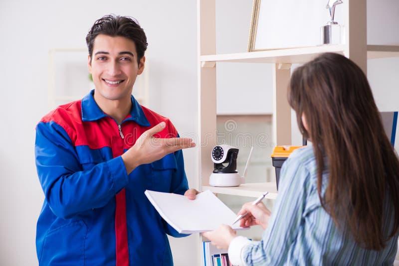 O cliente que obtém a câmera securty instalada em casa pelo contratante foto de stock
