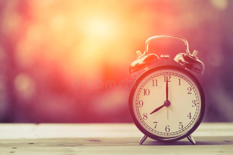 8 o`clock Clock Classic Vintage Retro Color Tone. On Wood Table with Sun Light royalty free stock image