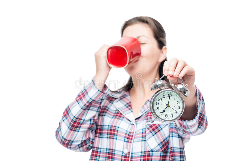 7 o`clock in the morning time to wake up and have a cup of coffe. E, portrait in pajamas on a white background stock photo