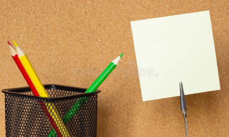 O close-up, as etiquetas e os lápis coloridos no fundo de uma cortiça embarcam, copiam o espaço imagem de stock royalty free