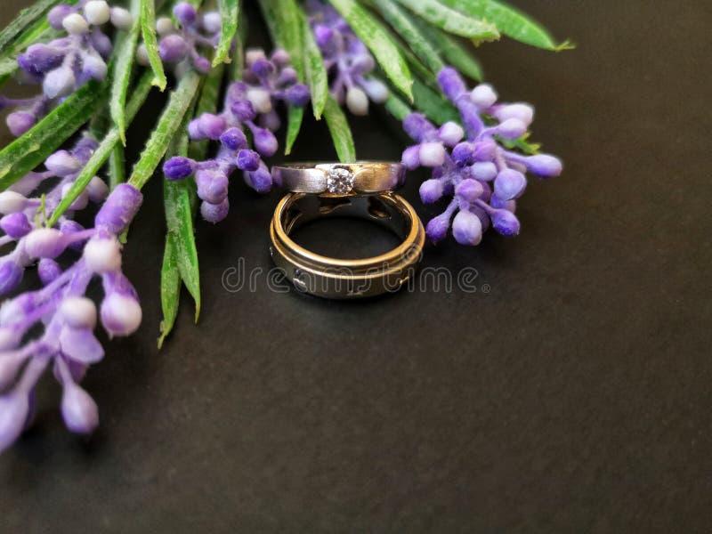 O close up com alianças de casamento com rosas bonitas floresce o fundo fotos de stock royalty free