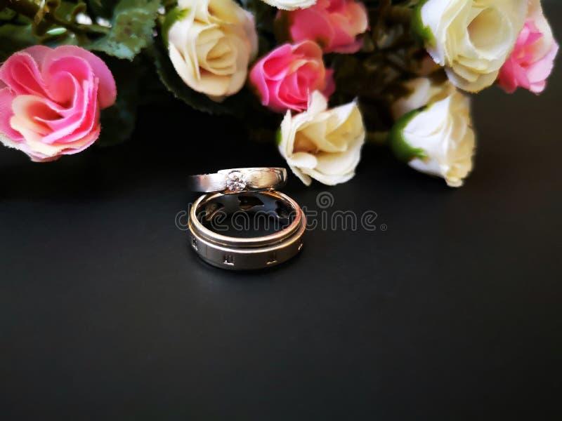 O close up com alian?as de casamento e as rosas bonitas florescem o fundo fotos de stock