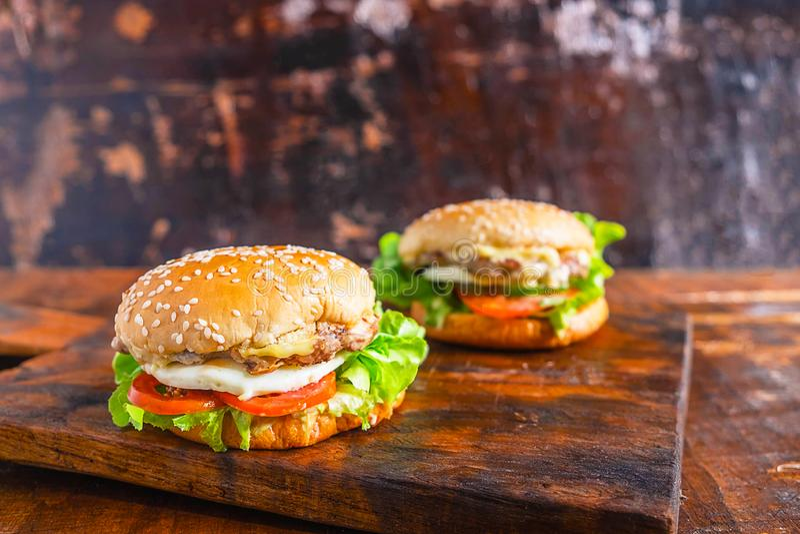 O close-up da casa fresca deliciosa fez o hamburguer com alface, queijo, cebola e tomate em uma prancha de madeira rústica na tab fotografia de stock royalty free