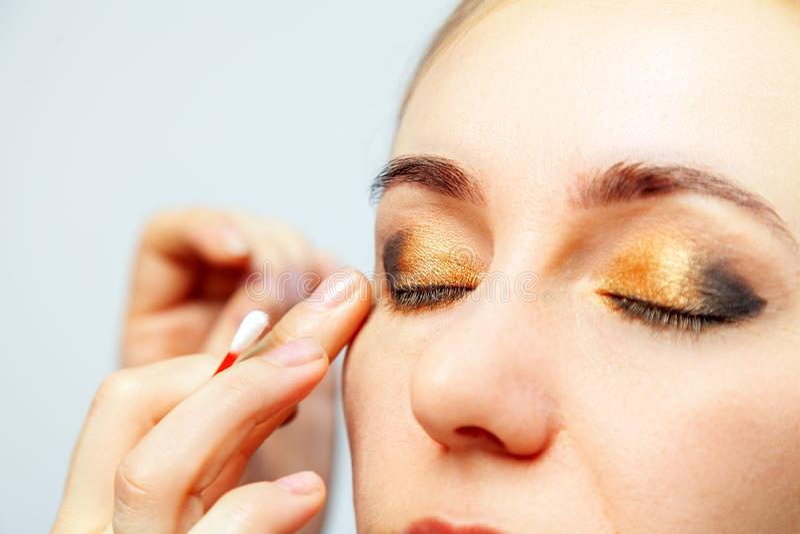 O close-up da composição dos olhos de um modelo com uma cara luz-colorida, o artista de composição guarda um cotonete de algodão  imagem de stock royalty free