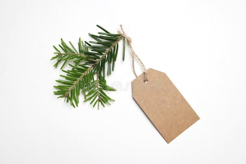 O close-up da etiqueta do presente do papel do ofício com corda e o abeto verde ramificam isolado no fundo branco Composição do N imagens de stock