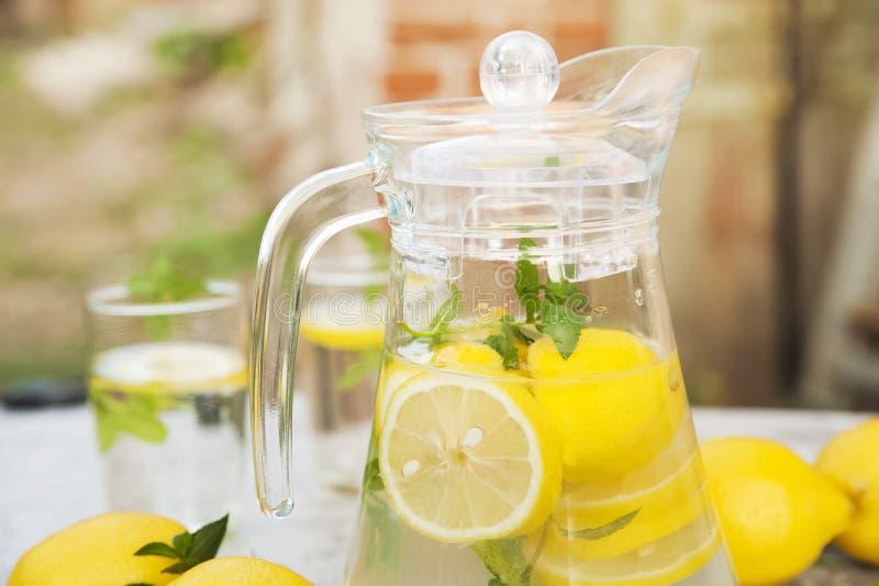 O close-up da limonada em um fundo concreto com limões cortou aberto Limões inteiros, hortelã, limonada fresca do verão na nature fotografia de stock