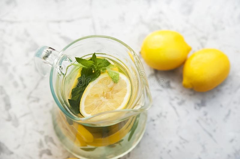 O close-up da limonada em um fundo concreto com limões cortou aberto Limões inteiros, hortelã, limonada fresca do verão na nature imagem de stock