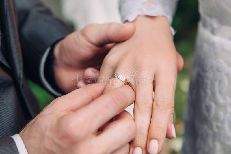 O close-up da mão do noivo põe uma aliança de casamento sobre o dedo das noivas, a cerimônia na rua, foco seletivo imagem de stock royalty free