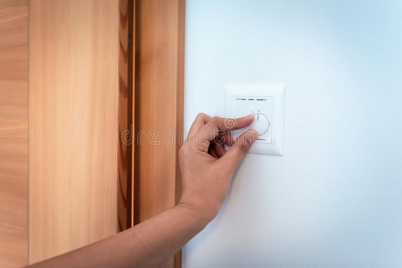 O close-up da mão da mulher é volta Heater Regulation Controller Button de ligar/desligar, elétrica ajusta o controle do painel d imagens de stock royalty free