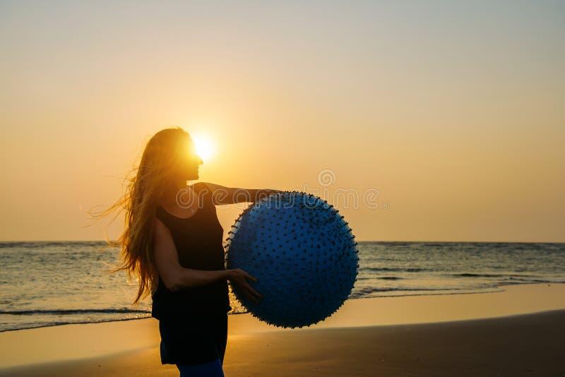 O close-up da mulher bonita nova com cabelo louro longo guarda a posição grande da bola da aptidão na praia à vista do sol de aju imagem de stock