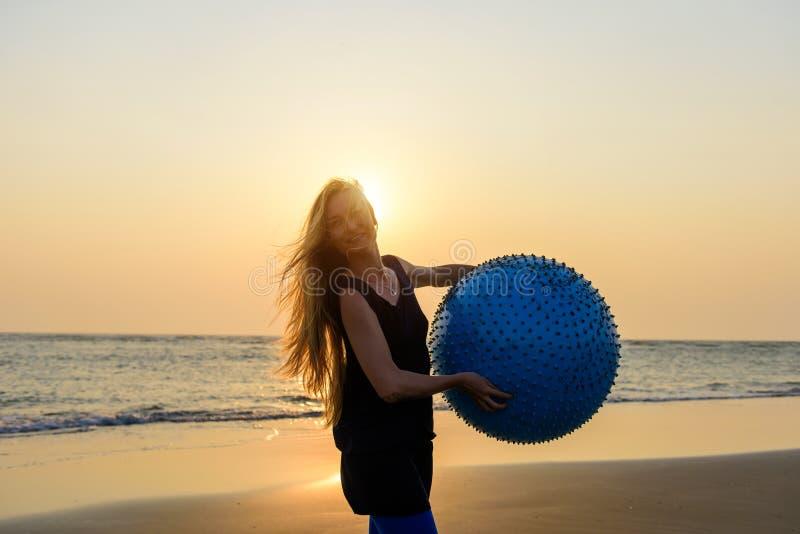O close-up da mulher bonita nova com cabelo louro longo guarda a posição grande da bola da aptidão na praia à vista do sol de aju fotografia de stock