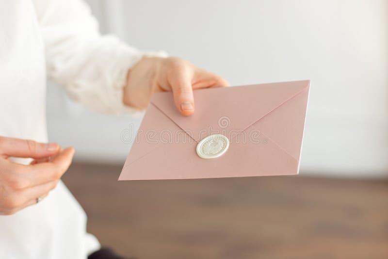 O close-up da mulher na camisa branca do estilo do negócio realiza em sua mão um cartão do convite, cartão, letra fotografia de stock royalty free