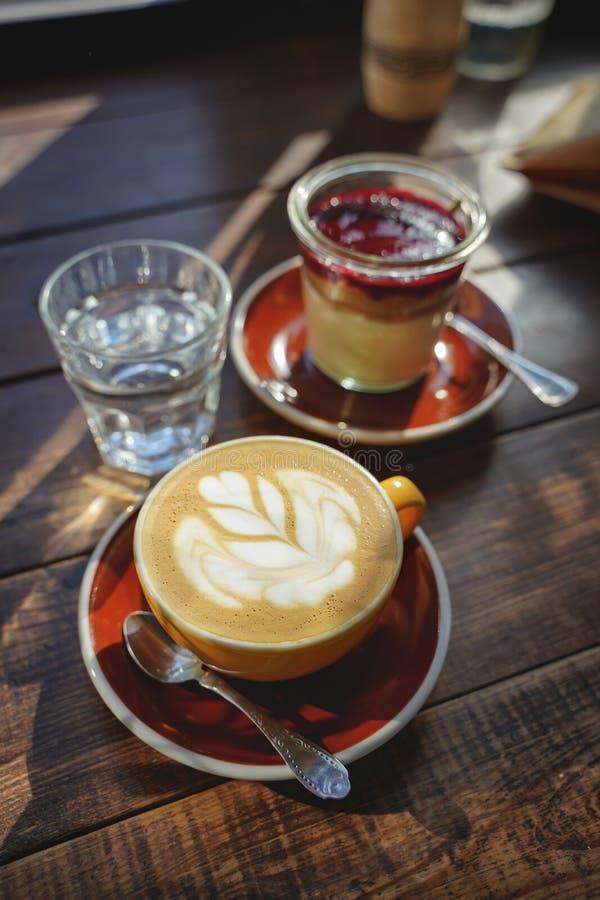 O close-up das mãos do ` s da mulher com um bolo da xícara de café, os raios do ` s do sol brilha através de uma janela no café M foto de stock