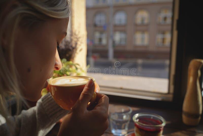 O close-up das mãos do ` s da mulher com um bolo da xícara de café, os raios do ` s do sol brilha através de uma janela no café M fotografia de stock