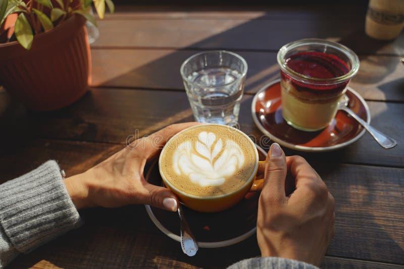 O close-up das mãos do ` s da mulher com um bolo da xícara de café, os raios do ` s do sol brilha através de uma janela no café M imagens de stock
