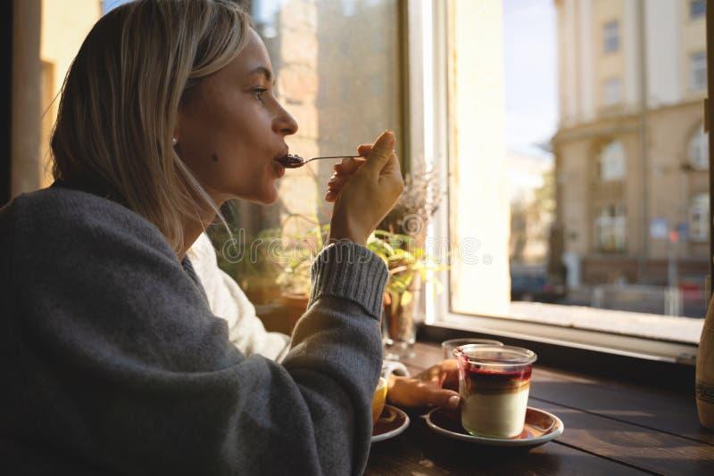 O close-up das mãos do ` s da mulher com um bolo da xícara de café, os raios do ` s do sol brilha através de uma janela no café M foto de stock royalty free