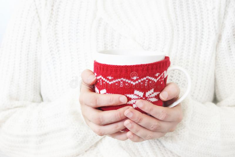 O close up das mãos do ` s da mulher no branco fez malha a camiseta que guarda a xícara de café Projeto do inverno do Natal Estoq foto de stock royalty free