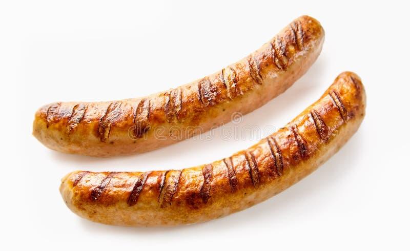 O close-up de dois grelhou salsichas alemãs no branco imagens de stock
