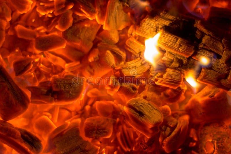 O close-up de incandescência do carvão vegetal remenda a textura quente do fundo imagens de stock