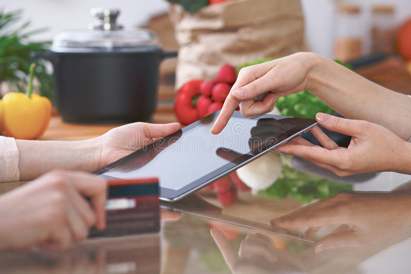 O close-up de quatro mãos humanas é gesticula sobre uma tabuleta na cozinha Amigos que têm o divertimento ao escolher o menu ou imagem de stock royalty free