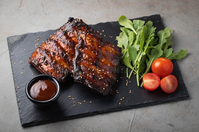 O close up de reforços de carne de porco grelhou com molho e rúcula do BBQ Petisco saboroso à cerveja em uma placa de pedra para  foto de stock