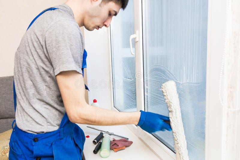O close-up de um homem em luvas uniformes e azuis lava janelas com raspador da janela Servi?o de limpeza da casa profissional imagens de stock royalty free