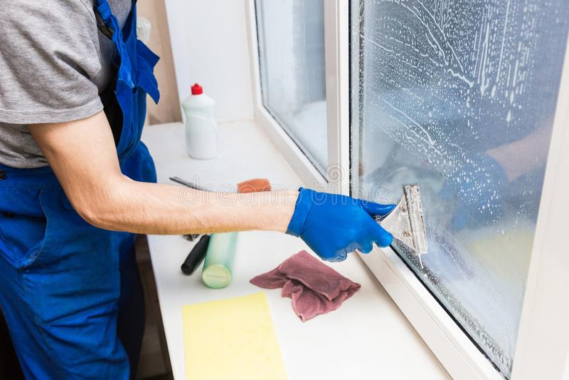 O close-up de um homem em luvas uniformes e azuis lava janelas com raspador da janela Servi?o de limpeza da casa profissional imagem de stock