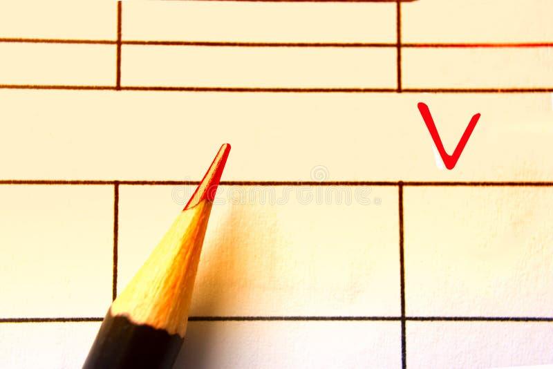 O close-up de um lápis vermelho, selecionando caixas de seleção checkout dentro o formulário, finança do negócio fotos de stock