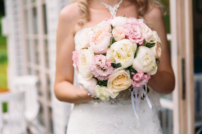 O close-up de um quadro colhido, a noiva em um vestido branco está guardando seu ramalhete do casamento das peônias, mostrando fl imagens de stock