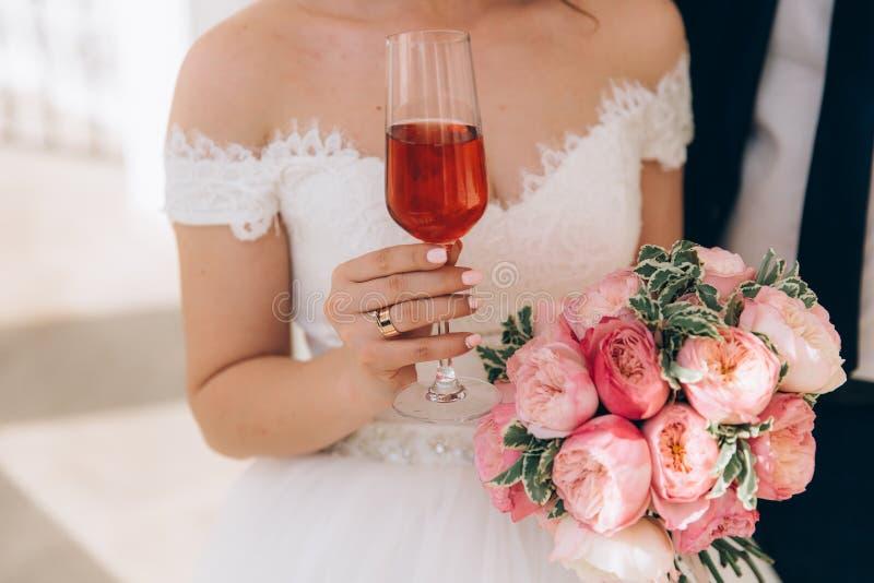 O close-up de um quadro colhido de uma noiva em um vestido branco está realizando em sua mão um ramalhete de peônias cor-de-rosa, fotografia de stock royalty free