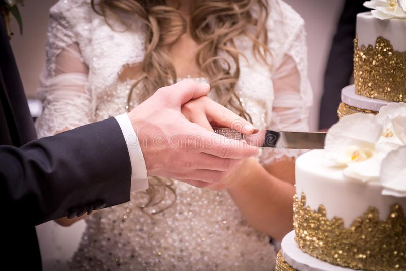 O close-up de um ` s dos pares do recém-casado entrega o corte de seu bolo de casamento fotos de stock royalty free