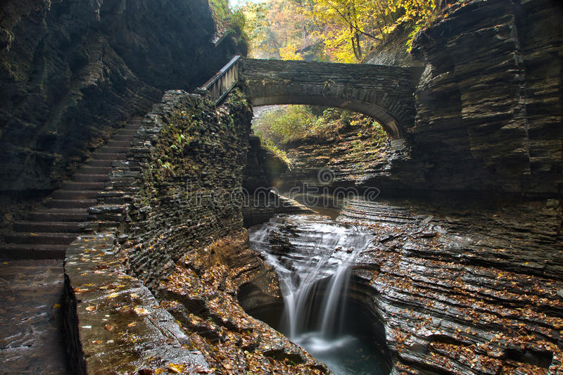 O close up de uma ponte de pedra sobre o arco-íris cai em Watkins Glen State Park imagem de stock