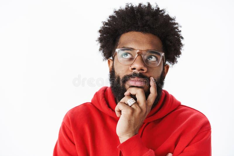 O close-up disparado da barba afro-americano pensativa da fricção do homem e de olhar o canto esquerdo superior focalizou, pensan imagens de stock royalty free