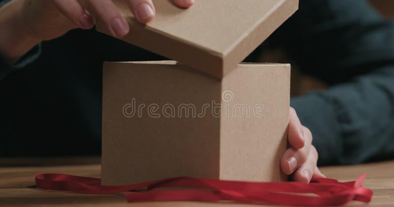 O close up disparado das mãos fêmeas novas abre a caixa de presente do papel do ofício com curva vermelha da fita fotografia de stock