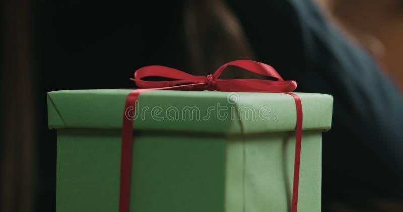 O close up disparado das mãos fêmeas novas desata a curva vermelha da fita na caixa de presente do papel do ofício foto de stock