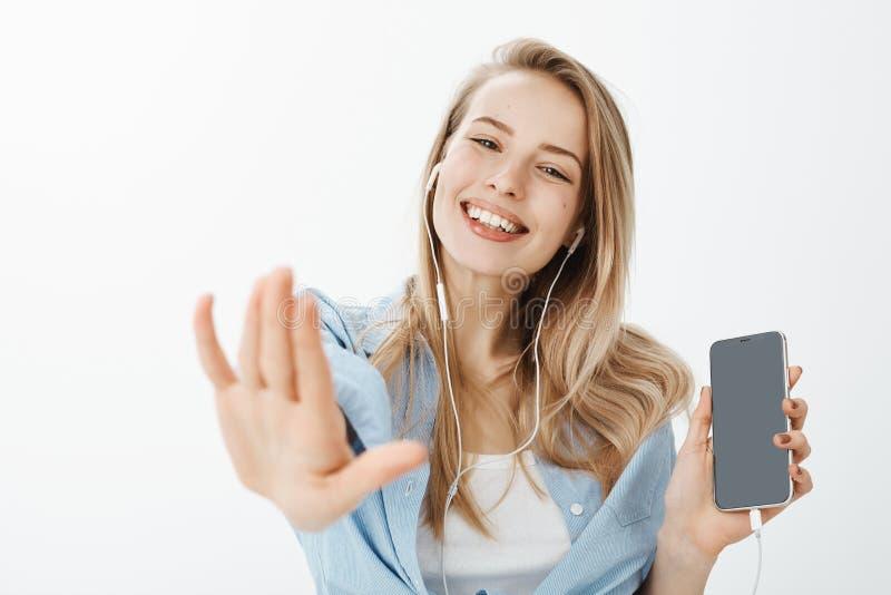 O close-up disparou da amiga europeia feliz despreocupada com cabelo justo, mostrando o smartphone e puxando a mão para a câmera fotografia de stock