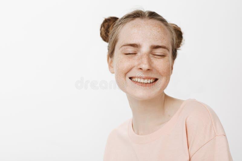 O close-up disparou da fêmea macia despreocupada com bolos bonitos penteado e sardas, sorrindo alegremente com olhos fechados e fotos de stock royalty free