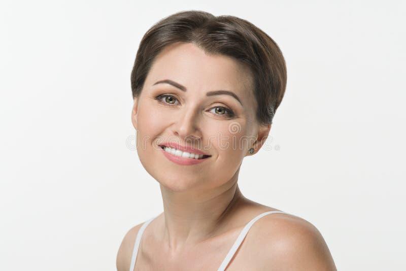 O close-up disparou da mulher adulta meados de bonita que sorri no fundo branco imagens de stock