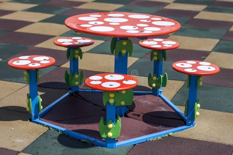 O close-up disparou da tabela pequena da criança redonda nova colorida brilhante e dos cinco tamboretes fora no revestimento de b imagem de stock