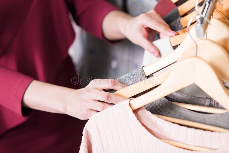 O close up disparou das mãos da mulher que escolhendo a roupa nova imagens de stock royalty free