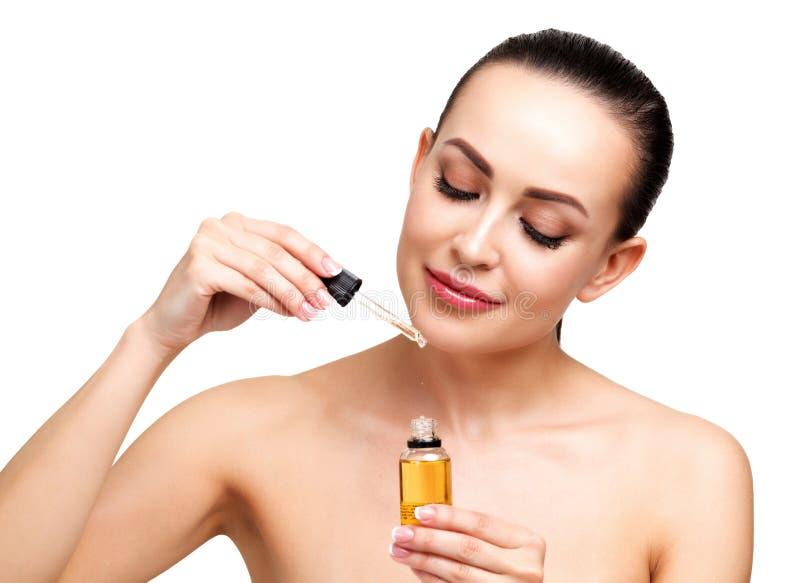 O close up disparou do óleo cosmético que aplica-se na cara do ` s da jovem mulher foto de stock