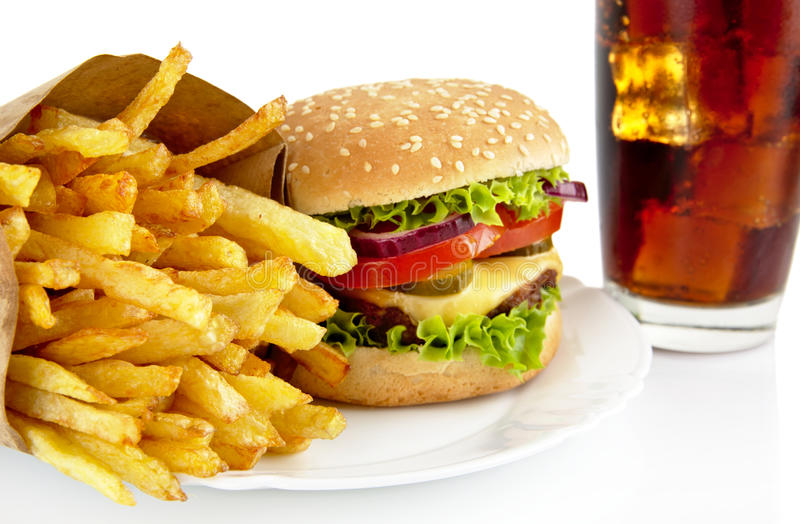 O close up disparou do cheeseburger, batatas fritas, vidro da cola na placa fotografia de stock royalty free