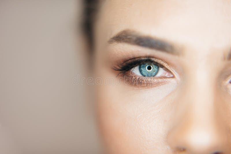 O close-up disparou dos olhos azuis bonitos da mulher fresca atrativa com composição natural no fundo bege Parte de fotografia de stock royalty free