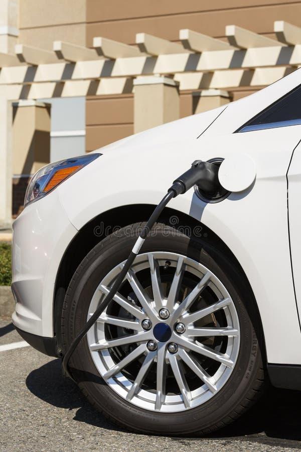 O close-up do automóvel do veículo do carro bonde com cabo obstruiu no conectado à estação de carregamento elétrica fotografia de stock