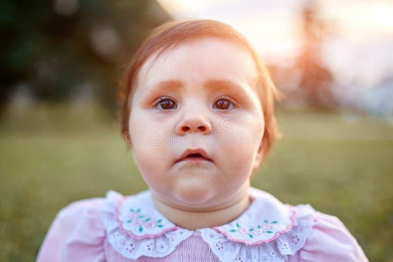 O close-up do bebê pequeno senta-se no cidade-parque contra o prado verde no dia de verão morno foto de stock