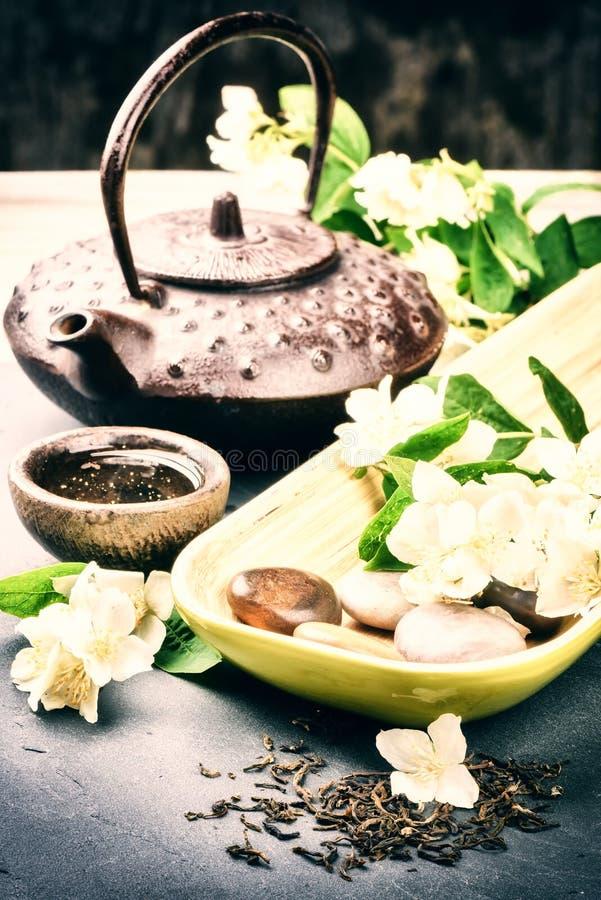 O close up do bule asiático, do chá secado e do jasmim fresco floresce foto de stock