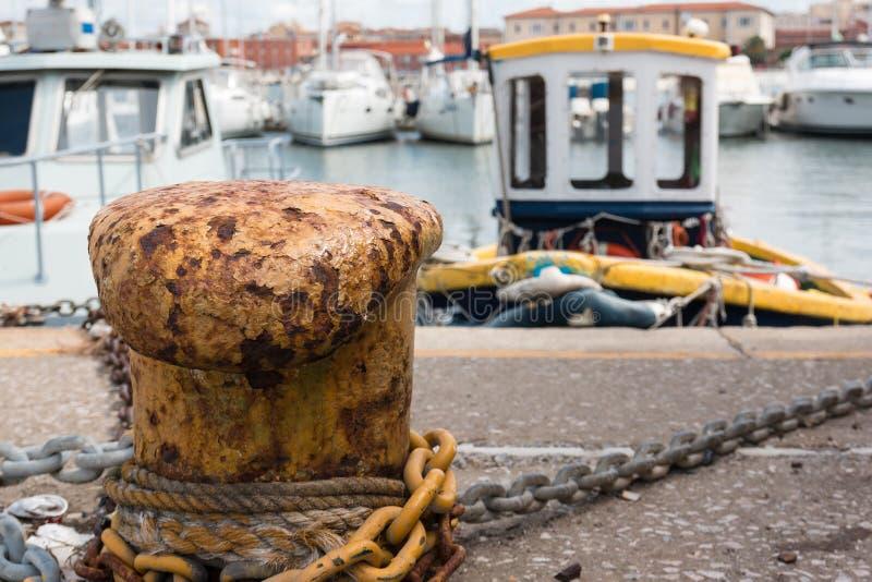 O close up do cabo da corda e do metal amarrado ao amarelo oxidou poste de amarração imagens de stock