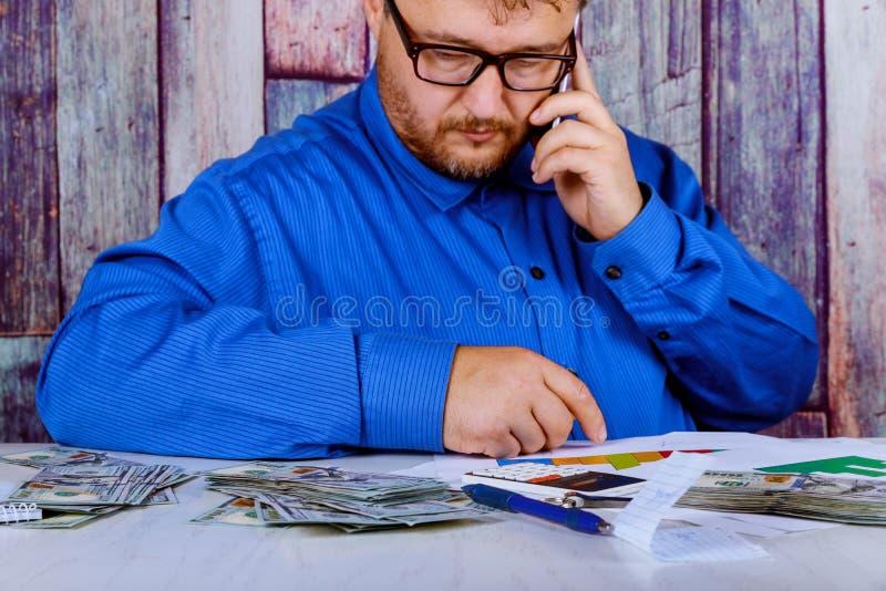 O close up do contador ou do banqueiro que fazem economias, finanças e mão guarda um telefonema esperto imagem de stock royalty free